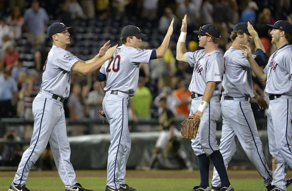 Photo - Virginia pitcher Brandon Waddell (20) celebrates with his teammates after Virginia defeated Vanderbilt 7-2 in Game 2 of the best-of-three NCAA baseball College World Series finals in Omaha, Neb., Tuesday, June 24, 2014. (AP Photo/Ted Kirk)