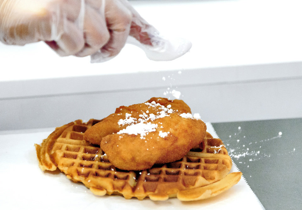Photo -  Powdered sugar is sprinkled on the chicken and waffles at Taste of Soul in Oklahoma City. [Photo by Chris Landsberger, The Oklahoman]
