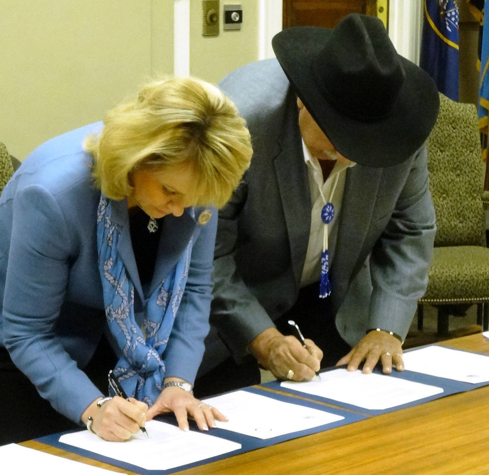 Photo - Gov. Mary Fallin and Kaw Nation Chairman Guy Munroe sign compacts Monday between the state of Oklahoma and the Kaw Nation.  PROVIDED - PROVIDED