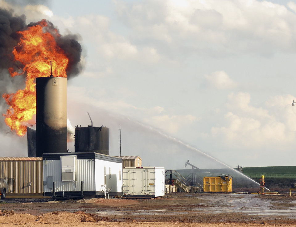 Photo - In this Monday, July 7, 2014 photo, firefighters battle a blaze caused by a lightning strike at a saltwater disposal facility near Alexander, N.D. In just over a month, lightning strikes have destroyed three of the state's more than 440 saltwater disposal facilities. Saltwater is a byproduct of oil production. (AP Photo/Josh Wood)