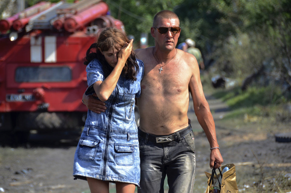 Photo - In this photo taken on Tuesday, July 2, 2014, Olga, who gave only her first name cries as a local man tries to help her, as they walk together from her burnt house after a Ukrainian Government forces airstrike in Luhanskaya village near Luhansk, eastern Ukraine, (AP Photo, Yuri Snegirev, Rossiyiskaya Gazeta)