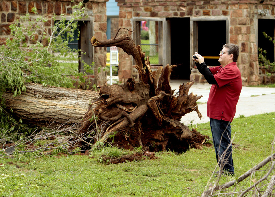 Mark Andrews, grandson of Abe Andrews for whom Andrews Park is named, takes a photograph Saturday of tornado damage at the park. PHOTO BY STEVE SISNEY, THE OKLAHOMAN STEVE SISNEY
