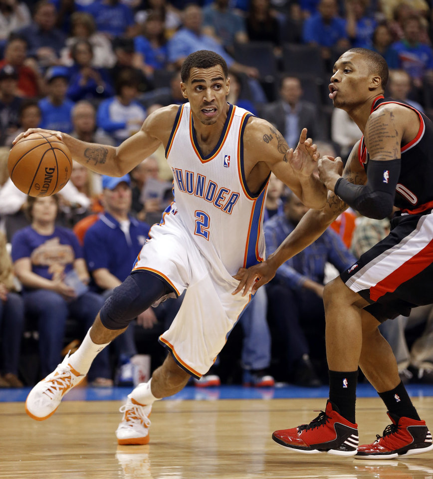 Photo - Thabo Sefolosha (2) drives to the lane guarded by Damian Lillard (0) as the Oklahoma City Thunder play the Portland Trail Blazers in NBA basketball at the Chesapeake Energy Arena in Oklahoma City, on Friday, Nov. 2, 2012.  Photo by Steve Sisney, The Oklahoman