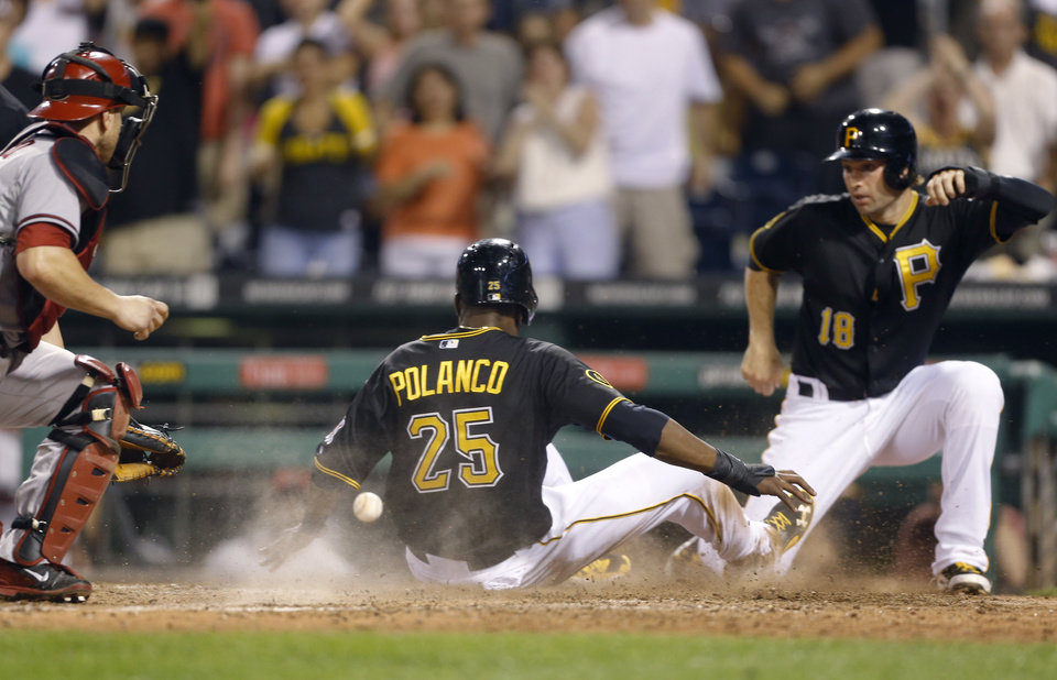 Photo - The ball gets past Pittsburgh Pirates' Tony Sanchez, left, as Pittsburgh Pirates' Gregory Polanco (25) scores behind Pittsburgh Pirates' Neil Walker (18) on a double by Starling Marte to tie the baseball game in the ninth inning on Tuesday, July 1, 2014, in Pittsburgh. The Pirates scored one more run runs in the ninth inning to win 3-2. (AP Photo/Keith Srakocic)