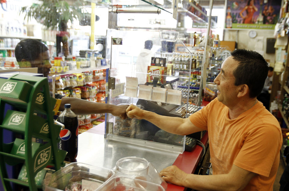 Photo -   In this Friday April 20, 2012 photo, James Oh, right, owner of Tom's Liquor on the corner of Florence and Normandie, greets a customer in his store in South Los Angeles. In the 20 years since the 1992 riots, residents of the city's largely black and Hispanic South Side complain that the area still is plagued by too few jobs, too few grocery stores and a lack of redevelopment that would bring more life to the area. (AP Photo/Matt Sayles)