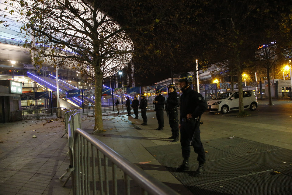 Photo - Police officer secure the  Stade de France stadium during the international friendly soccer France against Germany, Friday, Nov. 13, 2015 in Saint Denis, outside Paris. Two police officials say at least 11 people have been killed in shootouts and other violence around Paris. Police have reported shootouts in at least two restaurants in Paris. At least two explosions have been heard near the Stade de France stadium, and French media is reporting of a hostage-taking in the capital. (AP Photo/Michel Euler)