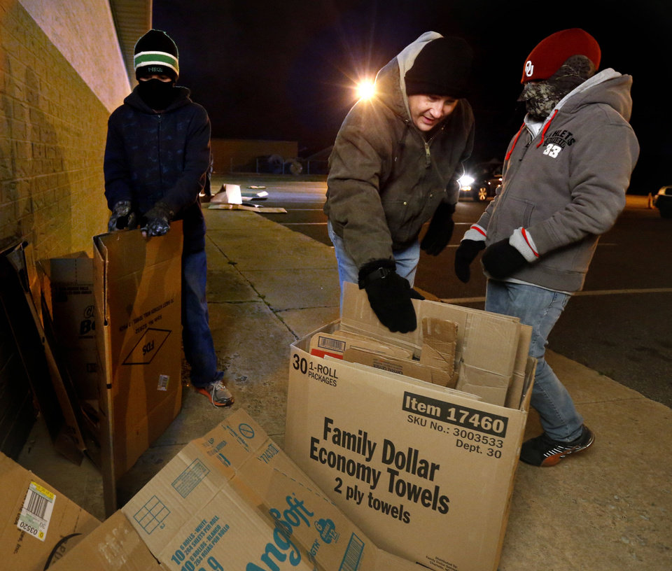 Scott Woodruff, center, helps his son Ben, 12, left, and friend Ryan Clement, 11, get cardboard boxes ready for sleeping as part of the Night in a Box event in Norman. PHOTOs BY STEVE SISNEY, THE OKLAHOMAN