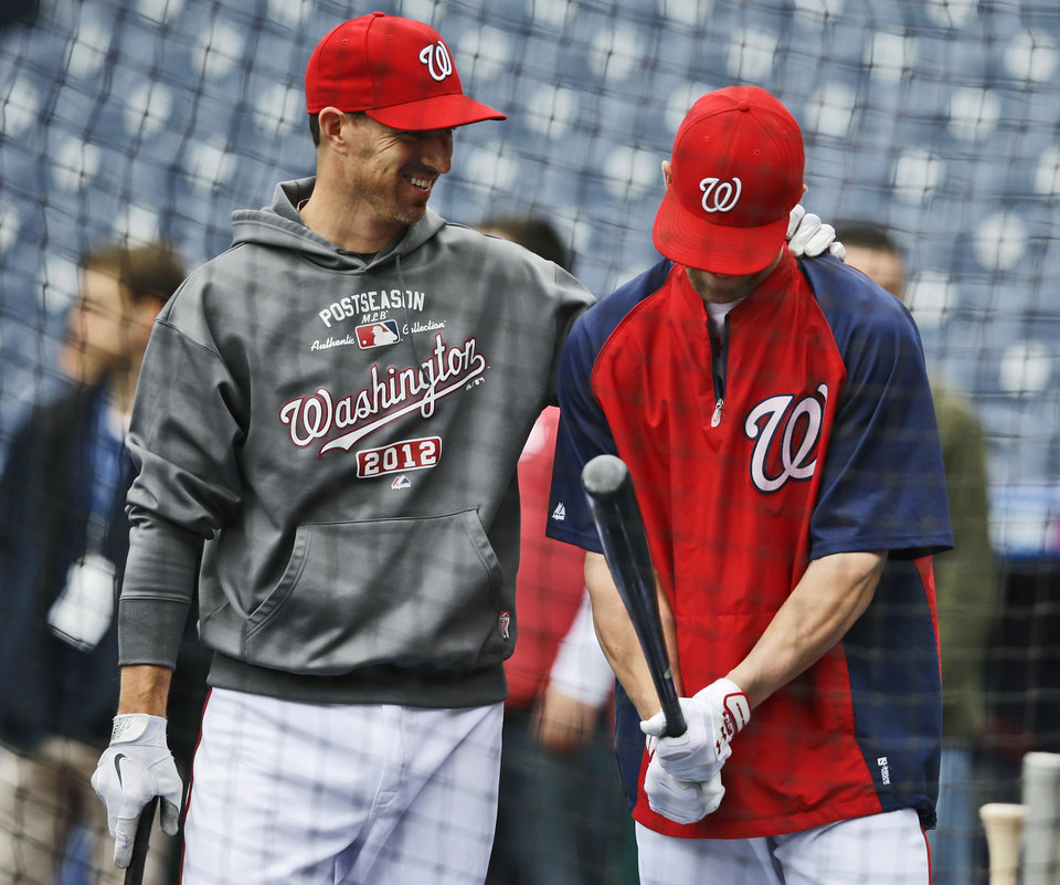 Washington Nationals' Adam LaRoche, left, talks with Bryce Harper during batting practice at Nationals Park, Tuesday, Oct. 9, 2012, in Washington. The Nationals are scheduled to host the St. Louis Cardinals in Game 3 of the National League division series on Wednesday. The best-of-five games series is tied 1-1. (AP Photo/Alex Brandon)
