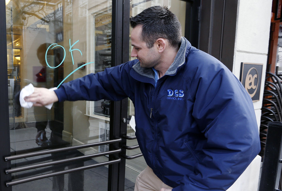 Antonio DaSilva, of Woburn, Mass., cleans a mark made on the entrance to a building on Boylston Street in Boston, Wednesday, April 24, 2013. Businesses opened and traffic was allowed to flow all the way down Boylston Street on Wednesday morning for the first time since two explosions at the Boston Marathon on April 15. (AP Photo/Michael Dwyer)