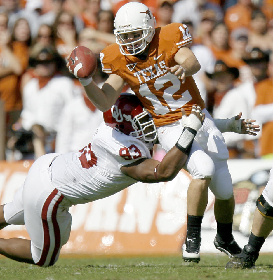 Photo - Colt McCoy of Texas tries to get away from OU's Gerald McCoy during the Red River Rivalry college football game between the University of Oklahoma Sooners (OU) and the University of Texas Longhorns (UT) at the Cotton Bowl in Dallas, Texas, Saturday, Oct. 17, 2009. Photo by Bryan Terry, The Oklahoman