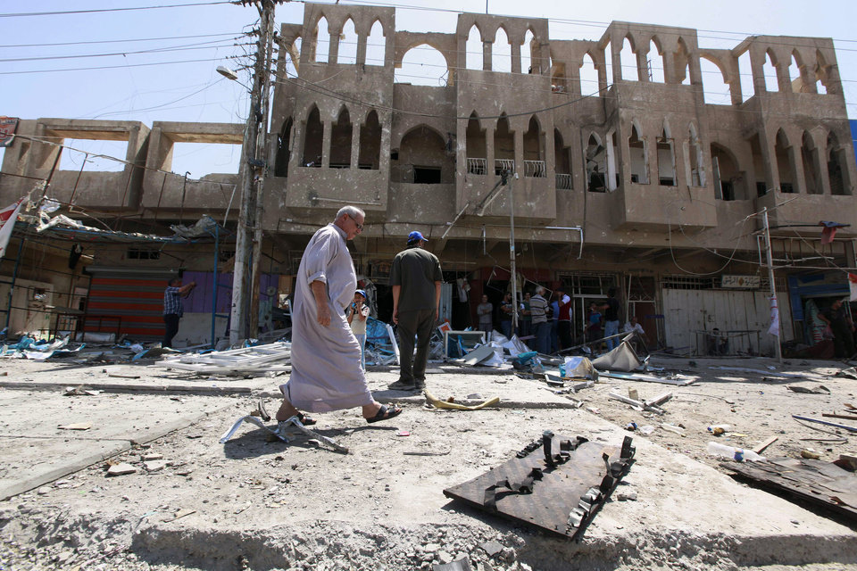 Photo - Civilians inspect the site of a bomb attack in the Jihad neighborhood in Baghdad, Saturday, July 19, 2014. A series of bombings, including three over a span of less than 10 minutes, killed and wounded dozens of people across Baghdad on Saturday, shaking the fragile sense of security the capital has maintained despite the Sunni militant offensive raging across northern and western Iraq. (AP Photo/Hadi Mizban)