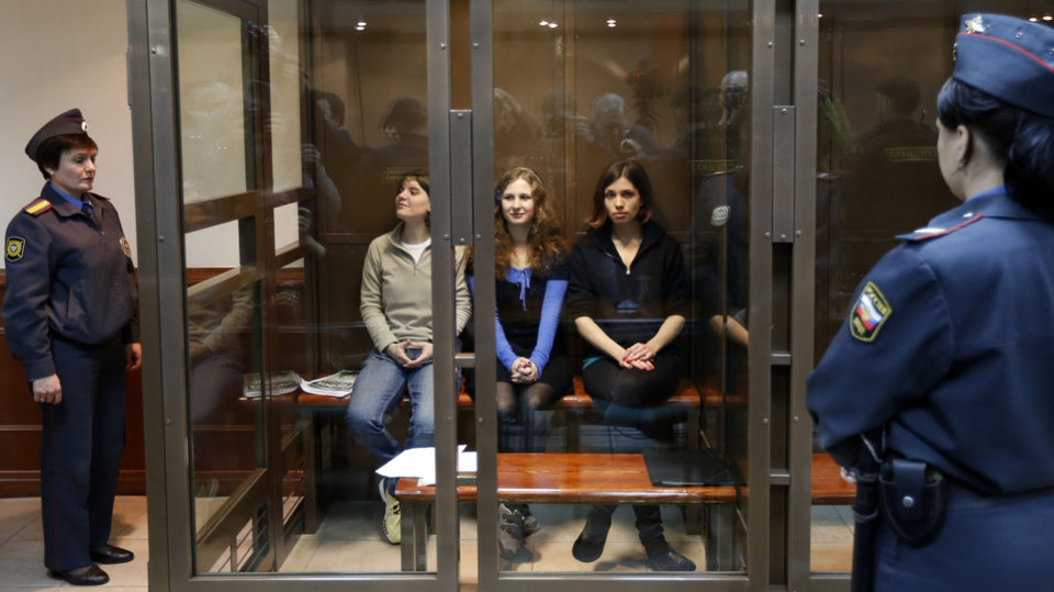 Photo -   CORRECTS THE LEFTS TO RIGHT Feminist punk group Pussy Riot members, from left, Yekaterina Samutsevich, Maria Alekhina, and Nadezhda Tolokonnikova sit in a glass cage at a court room in Moscow, Wednesday. Oct. 10, 2012. Three members of the punk band Pussy Riot are set to make their case before a Russian appeals court that they should not be imprisoned for their irreverent protest against President Vladimir Putin. Their impromptu performance inside Moscow's main cathedral in February came shortly before Putin was elected to a third term. The three women were convicted in August of hooliganism motivated by religious hatred and sentenced to two years in prison. (AP Photo/Sergey Ponomarev)