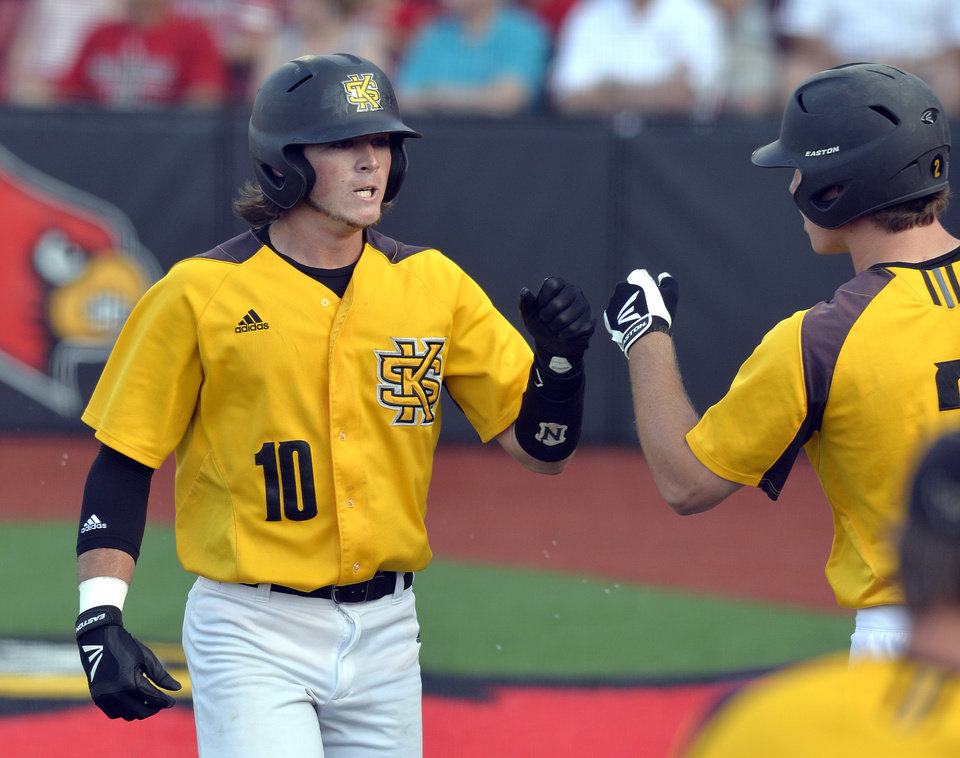 Photo - Kennesaw State's Kal Simmons, left, is congratulated by Max Pentecost after scoring against Louisville in the fourth inning of an NCAA college baseball tournament super regional game in Louisville, Ky., Friday, June 6, 2014. (AP Photo/Timothy D. Easley)