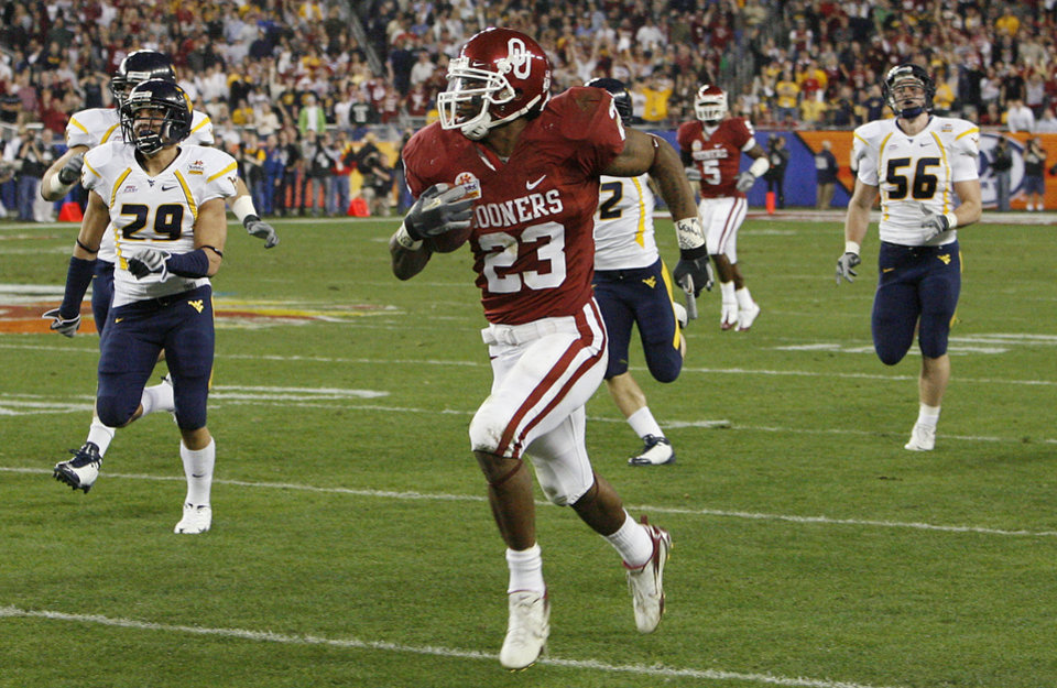 Photo - Oklahoma's Allen Patrick (23) takes the ball down the sideline past the West Virginia defease during the first half of the Fiesta Bowl college football game between the University of Oklahoma Sooners (OU) and the West Virginia University Mountaineers (WVU) at The University of Phoenix Stadium on Wednesday, Jan. 2, 2008, in Glendale, Ariz. 