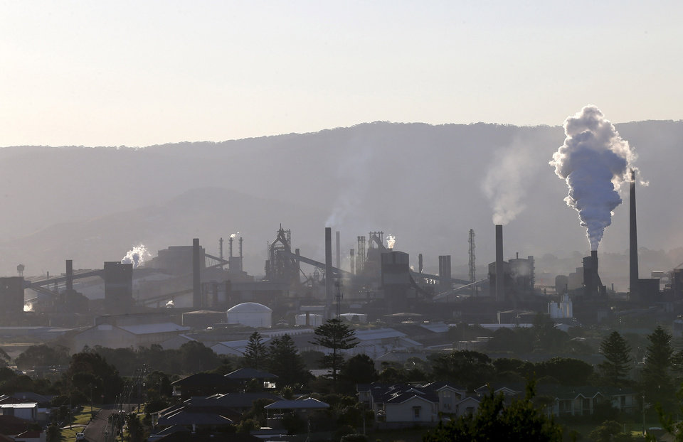 Photo - In this July 2, 2014 photo, smoke billows out of a chiming chimney stack of steel works factories in Port Kembla, 86 kilometers (53 miles) south of Sydney. The Senate is expected to vote as early as Monday, July 7, 2014, to repeal an unpopular, two-year-old tax charged to around 300 of the country's biggest carbon polluters. (AP Photo/Rob Griffith)