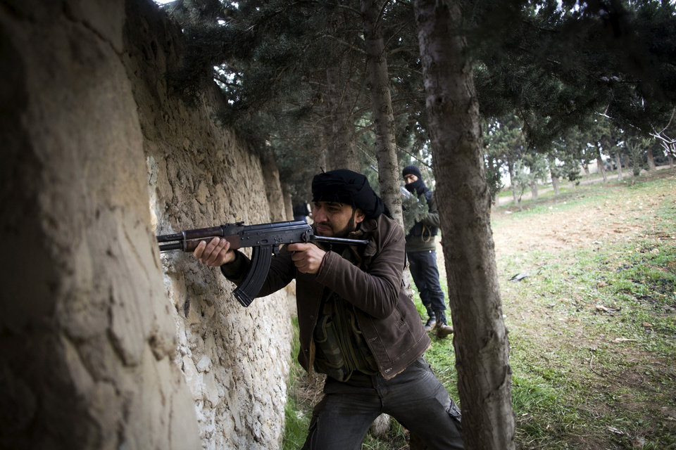A Free Syrian Army fighter fires at Syrian Army positions in Tal Sheer village, north of Aleppo province, Syria, Thursday, Dec. 13, 2012. (AP Photo/Manu Brabo) ORG XMIT: CAI122