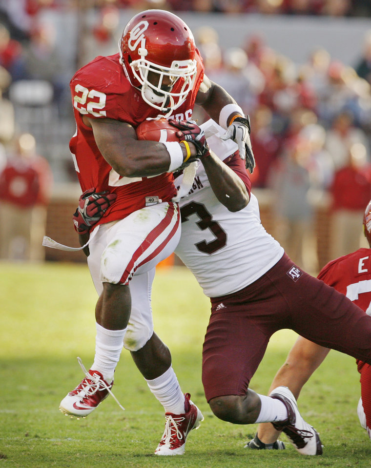 Photo - Oklahoma's Roy Finch (22) tries to shed a tackle by Texas A&M's Lionel Smith (3)during the second half of the college football game where the Texas A&M Aggies were defeated by the University of Oklahoma Sooners (OU) 41-25 at Gaylord Family-Oklahoma Memorial Stadium on Saturday, Nov. 5, 2011, in Norman, Okla. Photo by Steve Sisney, The Oklahoman