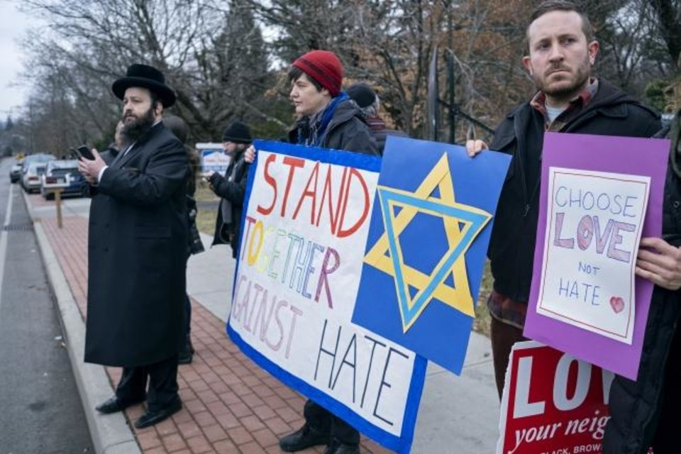 Photo -  Neighbors gather recently to show their support of the community near a rabbi's residence in Monsey, N.Y., after a stabbing the previous night during a Hanukkah celebration. [Craig Ruttle/The Associated Press]
