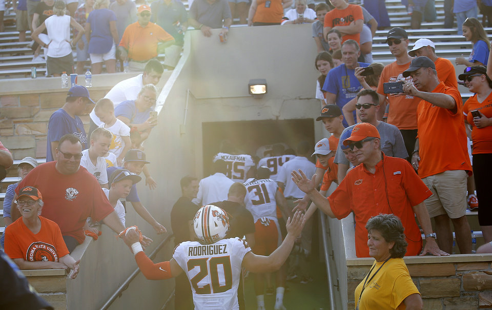 Photo - Oklahoma State's Malcolm Rodriguez (20) high fives fans following a college football game between the Oklahoma State University Cowboys (OSU) and the University of Tulsa Golden Hurricane (TU) at H.A. Chapman Stadium in Tulsa, Okla., Saturday, Sept. 14, 2019. [Sarah Phipps/The Oklahoman]