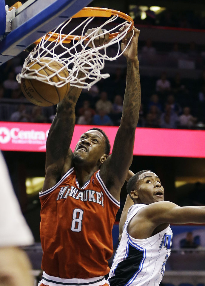 Photo - Milwaukee Bucks' Larry Sanders (8) dunks the ball over Orlando Magic's Maurice Harkless during the first half of an NBA basketball game, Wednesday, April 10, 2013, in Orlando, Fla. (AP Photo/John Raoux)