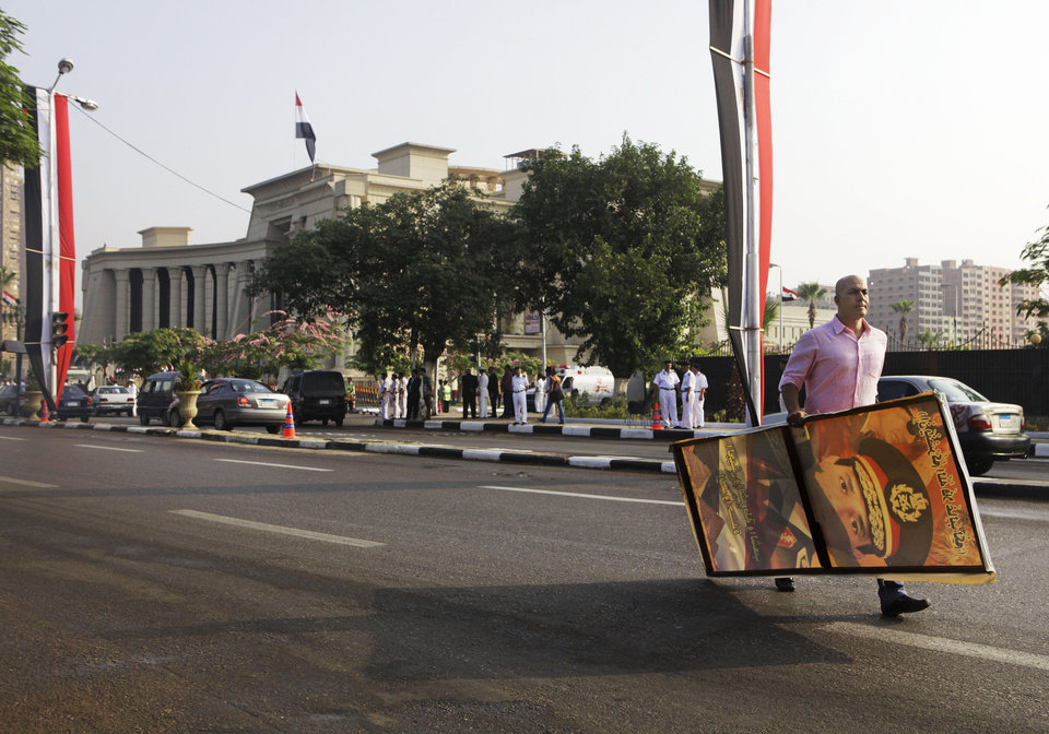 Photo - A supporter of Egyptian President-elect Abdel-Fattah el-Sissi carries a placard with a photo of him in front of the Supreme Constitutional Court, in Cairo, Egypt, Sunday, June 8, 2014. El-Sissi was sworn in on Sunday as president for a four-year term, taking the reins of power in a nation roiled since 2011 by deadly unrest and economic woes. (AP Photo/Amr Nabil)