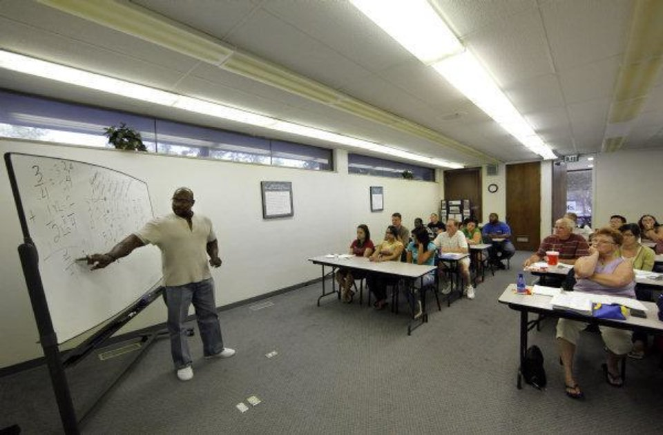 T.L. Tucker teaches a lesson on fractions and decimals during an Oklahoma City GED class at the Adult Learning Center on Thursday night. The loss of state funding will mean fewer classes, instructors and students. Photo by Garett Fisbeck, The Oklahoman Garett Fisbeck - Garett Fisbeck