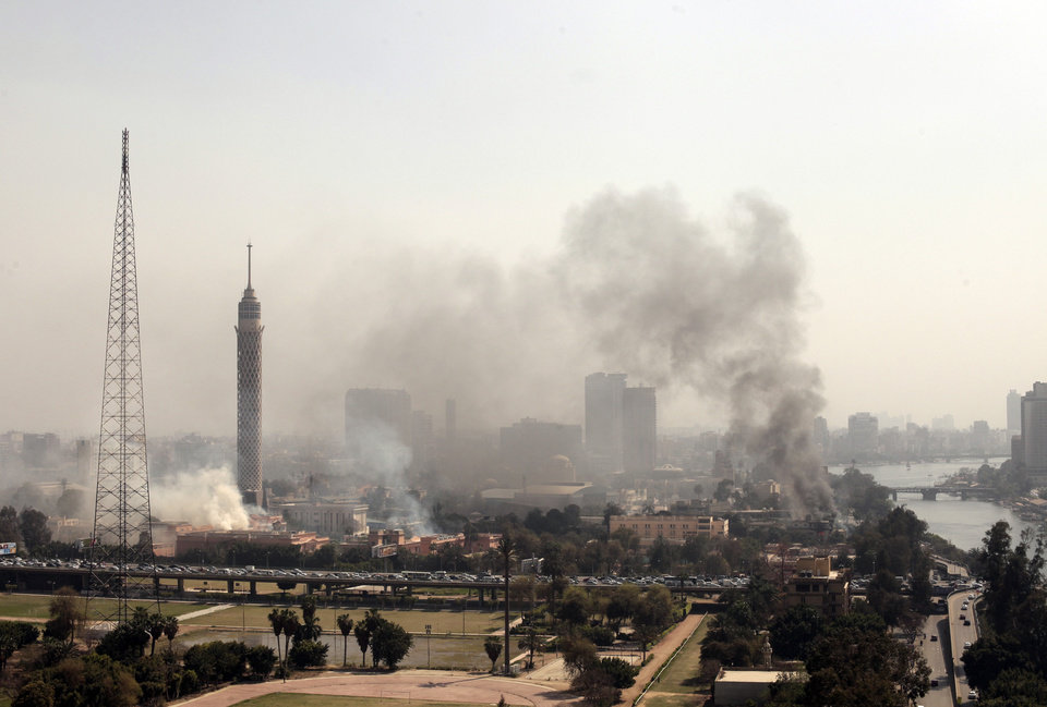 Photo - Smoke rises from the Police Officers Club, left, and the Egyptian Soccer Federation, right, after protesters set fire following a court verdict, in Cairo, Egypt, Saturday, March 9, 2013. Fans of Cairo's Al-Ahly club have stormed Egypt's soccer federation headquarters, set it ablaze after a court acquitted seven of nine police official on trial for their alleged part in deadly stadium melee. A fire also broke out Saturday in a nearby police club, but it was not immediately known whether Al-Ahly fans started the blaze there too. (AP Photo/Maya Alleruzzo)