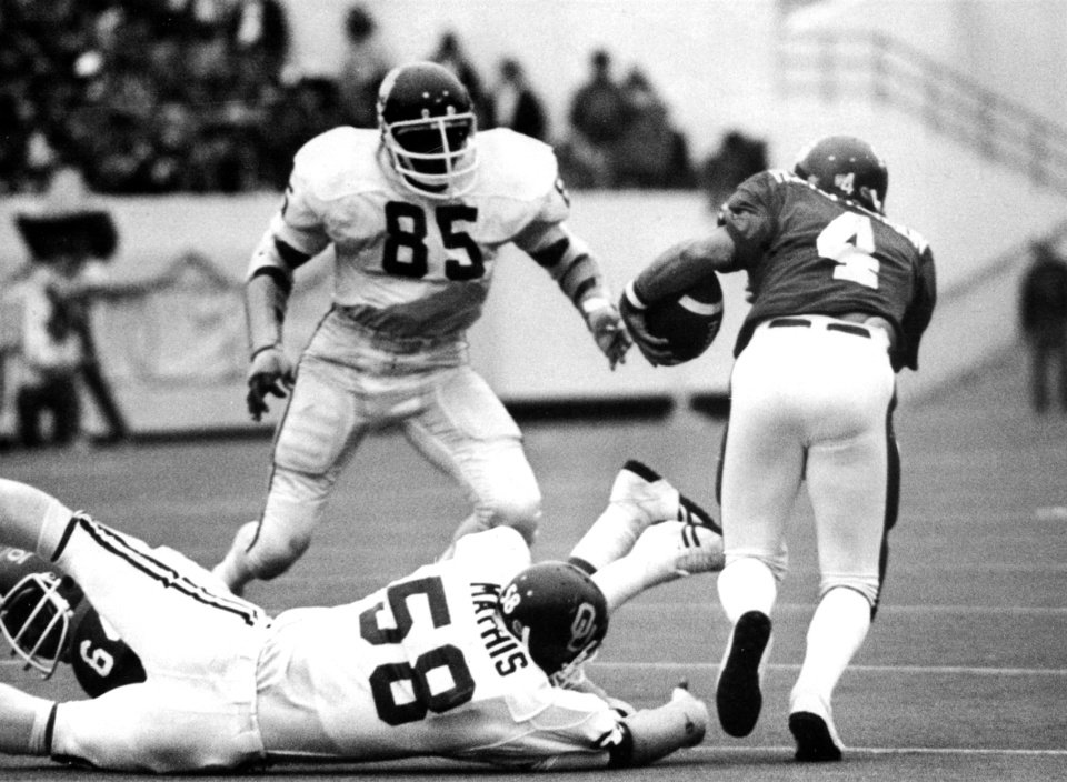 Oklahoma State University quarterback Randy Stephenson (4) eludes the grasp of OU's Reggie Mathis but OU linebacker Daryl Hunt (85) closes in on the Cowboy signal-caller during the Bedlam college football game, Nov. 5, 1977. The Sooners beat the Cowboys in Stillwater, 61-28. Staff photo by Jim Argo
