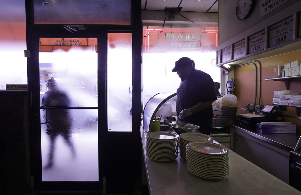 Photo - TAKES OUT HOT DOG REFERENCE - In this Monday, March 3, 2014 photo Nicholas Barros, a waiter and cook at Olneyville New York System of Providence works the grill as a customer walks up to the door in Providence, RI. The James Beard Foundation named the Rhode Island restaurant one of five