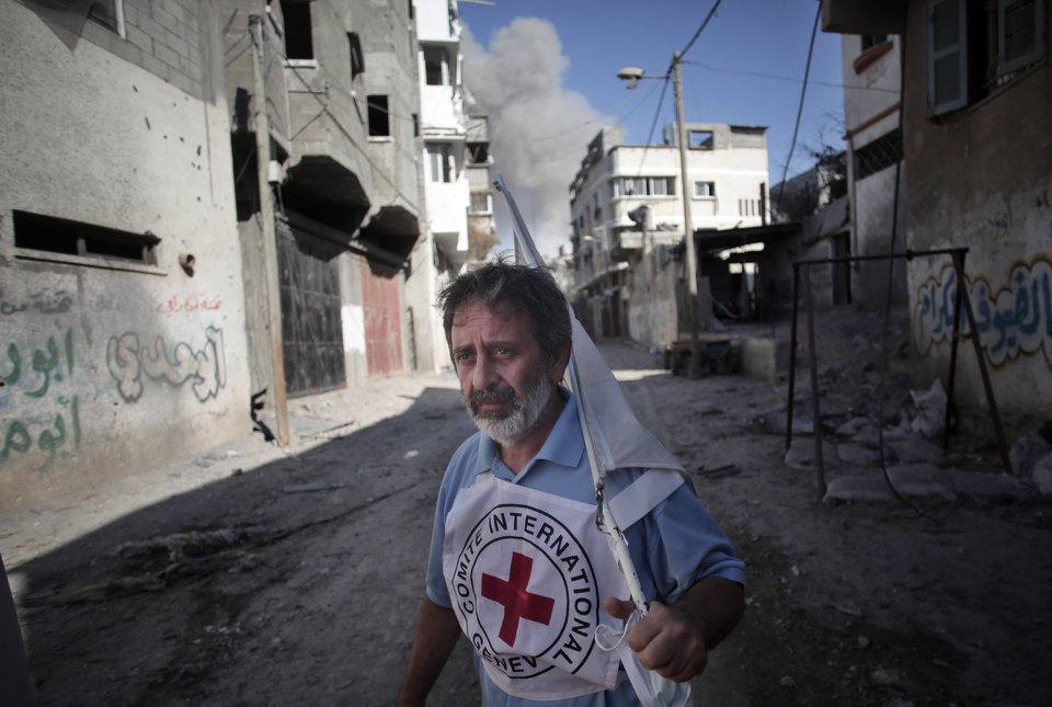 Photo - A International Red Cross employee runs for cover after an Israeli strike during a two-hour temporary ceasefire in Gaza City's Shijaiyah neighborhood, Wednesday, July 23, 2014. Israeli troops battled Hamas militants on Wednesday near a southern Gaza Strip town as U.S. Secretary of State John Kerry reported progress in efforts to broker a truce in a war that has so far killed more than 650 Palestinians and at least 30 Israelis. (AP Photo/Khalil Hamra)