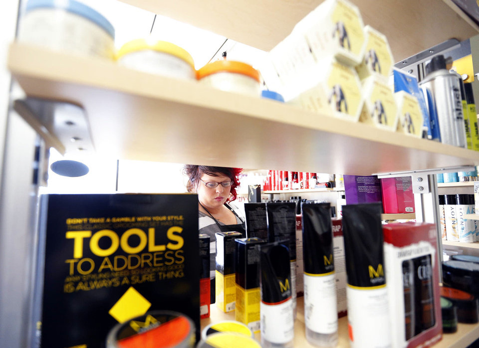 Photo - Bridgette Smith organizes products at Supercuts at 23V Retail Plaza, 2519 NW 23, a redevlopment project by Baker First Commercial Real Estate Services.  SARAH PHIPPS - The Oklahoman