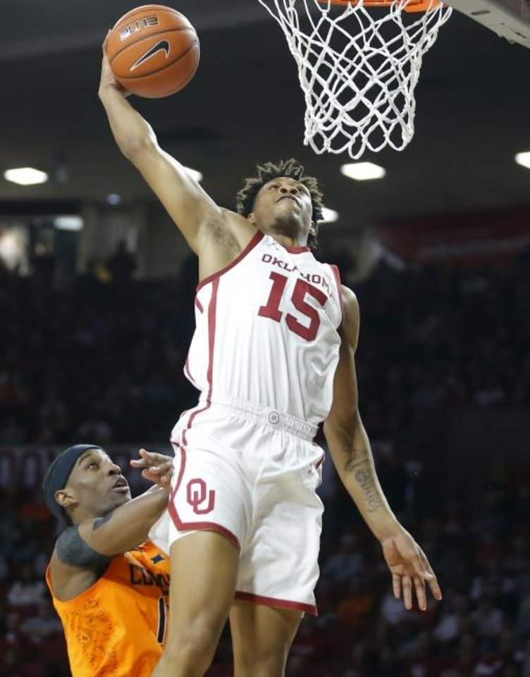 Photo -  OU's Alondes Williams (15) dunks over OSU's Cameron McGriff (12) during the Sooners' 82-69 win Feb. 1 in Norman. [Bryan Terry/The Oklahoman]
