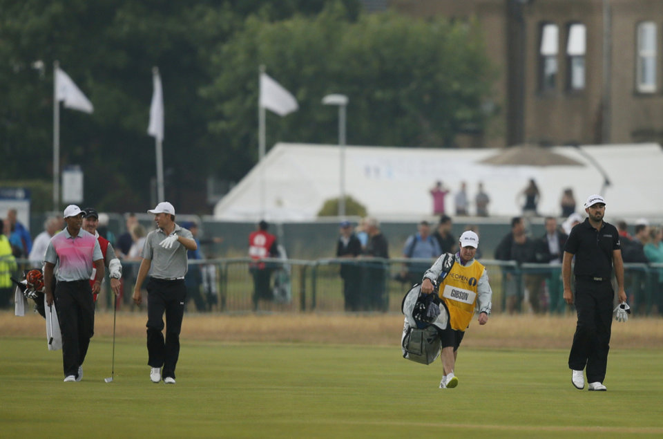 Photo - Tiger Woods of the US, left, walks along the 18th fairway with Jordan Spieth of the US and Rhein Gibson of Australia, right, during the third day of the British Open Golf championship at the Royal Liverpool golf club, Hoylake, England, Saturday July 19, 2014. (AP Photo/Alastair Grant)