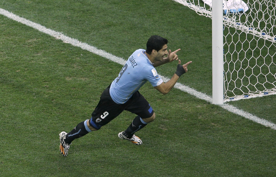 Photo - Uruguay's Luis Suarez celebrates scoring the opening goal during the group D World Cup soccer match between Uruguay and England at the Itaquerao Stadium in Sao Paulo, Brazil, Thursday, June 19, 2014.  (AP Photo/Michael Sohn)