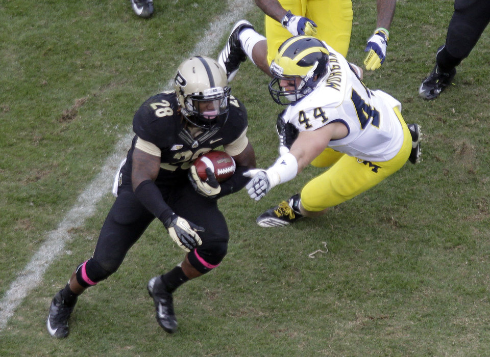 Purdue cornerback Josh Johnson (28) gets past Michigan linebacker Desmond Morgan as he runs during the second half of an NCAA college football game in West Lafayette, Ind., Saturday, Oct. 6, 2012. Michigan defeated Purdue 44-13. (AP Photo/Michael Conroy)