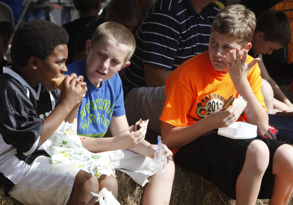 Photo - Perkins-Tryon Intermediate School students Ayron Lawson, left, Cade McCutchen, and Justin Lay have lunch during school day of the Oklahoma Wildlife Expo at the Lazy E Arena and Ranch in Guthrie, OK, Friday, September 28, 2012,  By Paul Hellstern, The Oklahoman