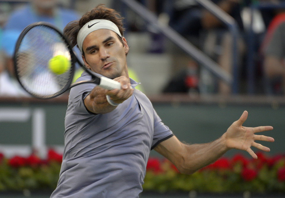 Photo - Roger Federer, of Switzerland, returns a shot against Tommy Haas, of Germany, during a match at the BNP Paribas Open tennis tournament on Wednesday, March 12, 2014, in Indian Wells, Calif. (AP Photo/Mark J. Terrill)