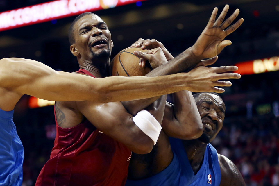 Oklahoma City Thunder\'s Thabo Sefolosha, left, and Kendrick Perkins, right, defend against Miami Heat\'s Chris Bosh, center, during the first half of an NBA basketball game, Tuesday, Dec. 25, 2012, in Miami. (AP Photo/J Pat Carter) ORG XMIT: FLJC104