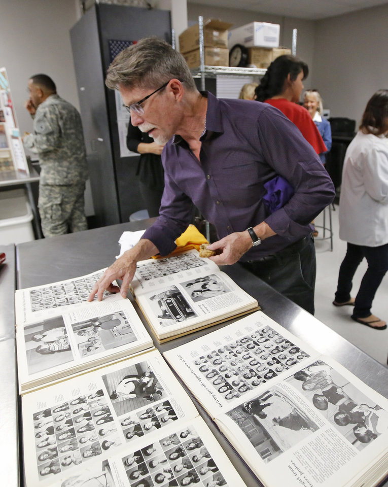 Photo -  Celebrity chef and Northwest Classen alumni Rick Bayless looks at some of his old yearbook photos during a tour of the school campus in Oklahoma City, Monday October, 19 2015. Photo By Steve Gooch, The Oklahoman