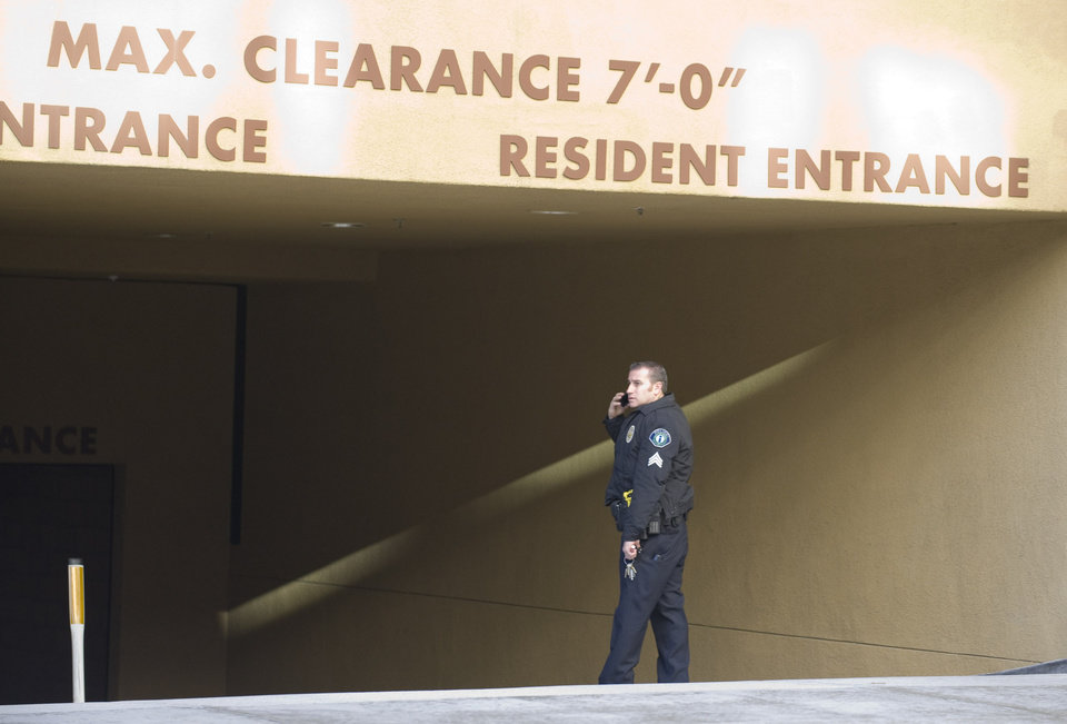 Photo - An Irvine police officer talks on the phone Monday, Feb. 4, 2013 at the entrance to the parking garage where two people were found shot to death in their car in Irvine, Calif., Sunday night, Feb. 3. Police in Orange County say they have no motive for a shooting that killed California State University, Fullerton assistant college basketball coach Monica Quan and her fiance, Keith Lawrence, whose bodies were found in a parked car. (AP Photo/The Orange County Register, Sam Gangwer)   MAGS OUT; LOS ANGELES TIMES OUT