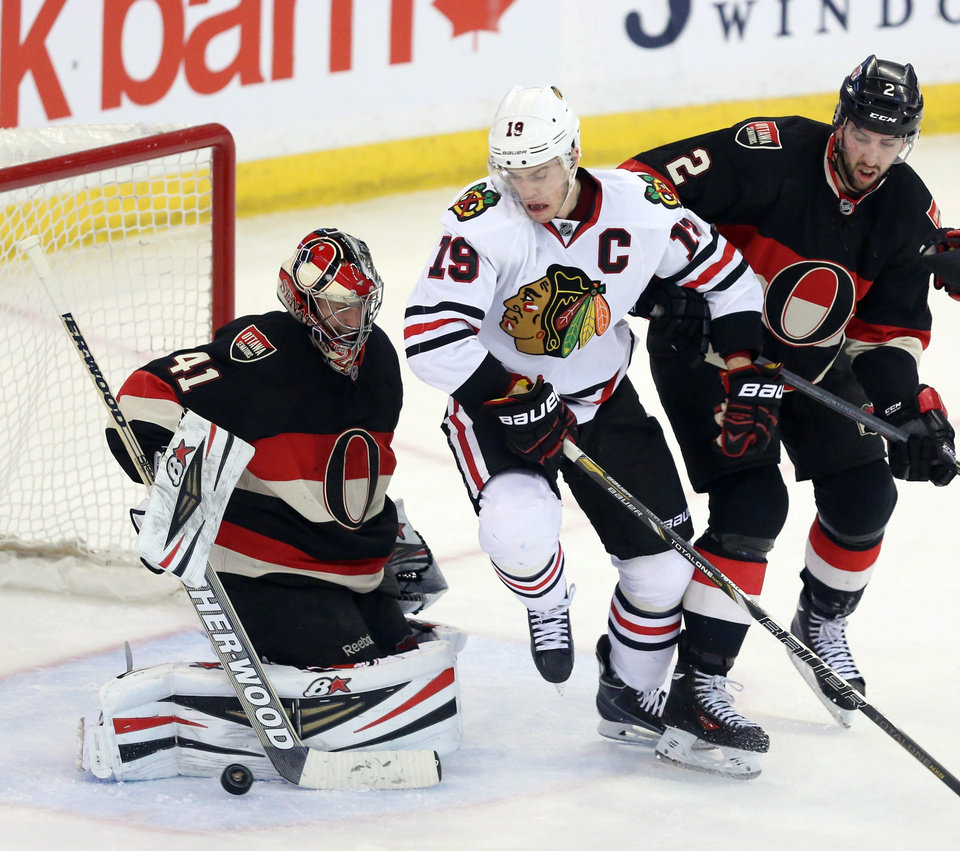 Photo - Ottawa Senators goaltender Craig Anderson (41) clears the puck as teammate Jared Cowen (2) and Chicago Blackhawks' Jonathan Toews (19) battle in front of the net during second-period NHL hockey game action in Ottawa, Ontario, Friday, March 28, 2014. (AP Photo/The Canadian Press, Fred Chartrand)