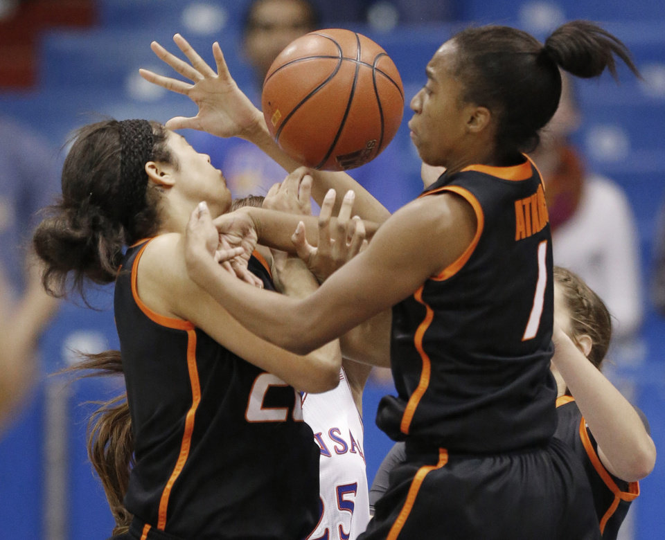 Oklahoma State guards Brittney Martin, left, and Brittany Atkins, right, get tangled while rebounding against Kansas forward Caelynn Manning-Allen, back, during the first half of an NCAA college basketball game in Lawrence, Kan., Wednesday, Jan. 22, 2014. (AP Photo/Orlin Wagner)