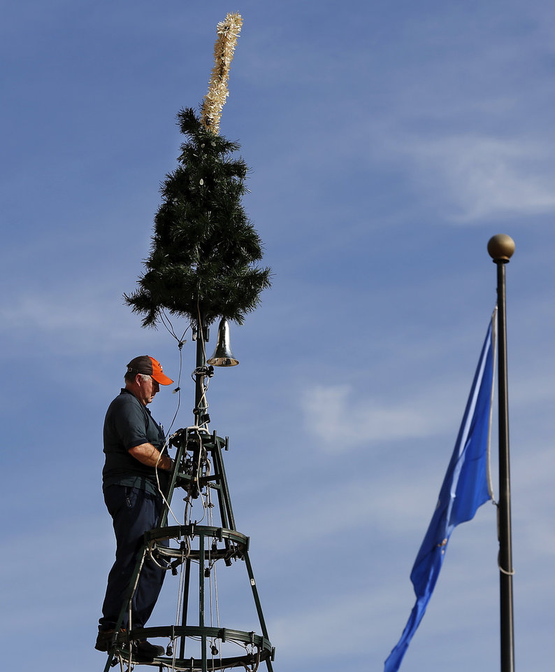 At the top of the tree is Bud Dolan, the State Capitol Park contract administrator. He is assigned to the division of capitol asset management/ office of facilities services. He has been erecting the Capitol Christmas tree for 13 years. Workers began assembling the Christmas tree on the south plaza of the state Capitol Monday afternoon, Nov. 19, 2012. The 30-foot artificial pine tree has 256 branches and 2000 lights. The tree was donated to the state by the Weyerhaeuser Company Foundation seven years ago. Trustees from the Hillside Community Correctional Center assisted state employees in attaching the greenery and ornaments onto the frame. Photo by Jim Beckel, The Oklahoman