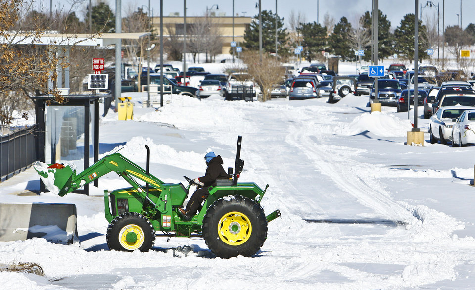 Photo - Crews work to clear paths in the satellite parking lots at Will Rogers Airport on Wednesday, Feb. 2, 2011, Oklahoma City, Okla.   Photo by Chris Landsberger, The Oklahoman