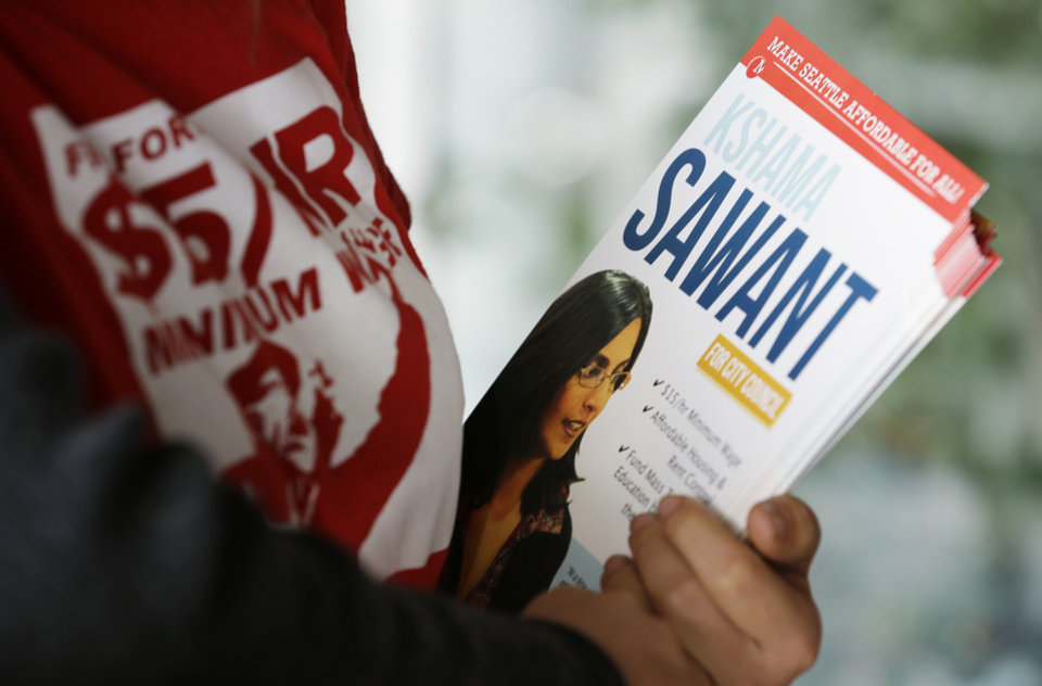 Photo - In this photo taken Nov. 4, 2013, a supporter of Socialist candidate for Seattle City Council Kshama Sawant, holds campaign materials outside a City Council meeting in Seattle. Sawant is challenging four-term Councilman Richard Conlin. (AP Photo/Ted S. Warren)
