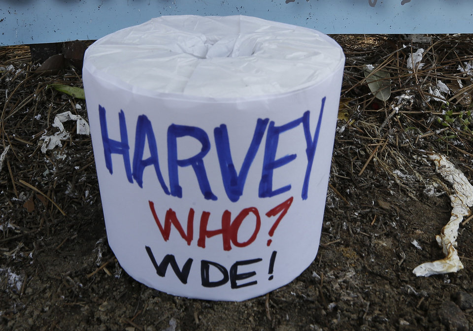 Photo - A roll of toilet paper with a message sits on the ground near the poisoned oak trees at Toomer's Corner at the entrance to Auburn University in Auburn, Ala., Tuesday, April 23, 2013. Harvey Updyke Jr. is serving a jail term after pleading guilty to spiking the oaks with a powerful herbicide, and experts say they can't be saved. Workers used chainsaws and heavy equipment to remove what's left of the once-lush hardwoods at Toomer's Corner. Auburn fans traditionally roll the trees with toilet paper after a big victory, and tens of thousands rolled the trees after the spring football game last Saturday. (AP Photo/Dave Martin)