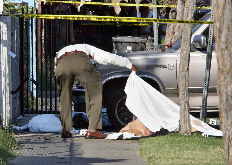 FILE - In this June 30, 2006 file photo, an investigator views one of three gunshot victims on 49th Street in South Los Angeles. A gunman toting an assault rifle got out of a vehicle and shot to death 10-year-old David Marcial, the boy's 22-year-old uncle and a 17-year-old neighbor. David's 12-year-old brother, Sergio, survived. In the wake of the Dec. 14, 2012 mass shooting at Sandy Hook Elementary School in the small town of Newtown, Conn., there is now much political discussion about gun control. For urban advocates, this new emphasis on gun control is long overdue. (AP Photo/Reed Saxon, File)