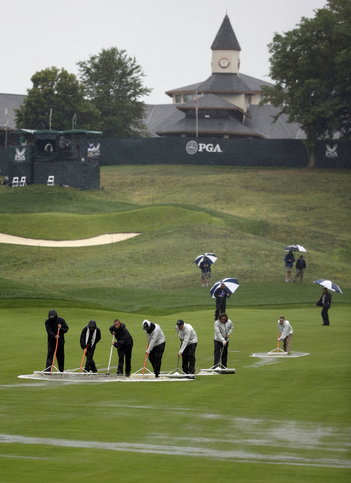 Photo - Members of the grounds crew push water off the first fairway during the second round of the PGA Championship golf tournament at Valhalla Golf Club on Friday, Aug. 8, 2014, in Louisville, Ky. (AP Photo/John Locher)