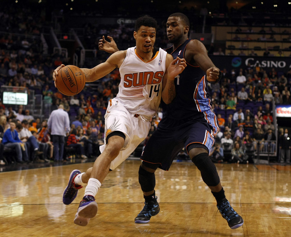 Photo - Phoenix Suns shooting guard Gerald Green (14) drives against Charlotte Bobcats small forward Michael Kidd-Gilchrist (14) in the fourth quarter during an NBA basketball game on Saturday, Feb. 1, 2014, in Phoenix. (AP Photo/Rick Scuteri)