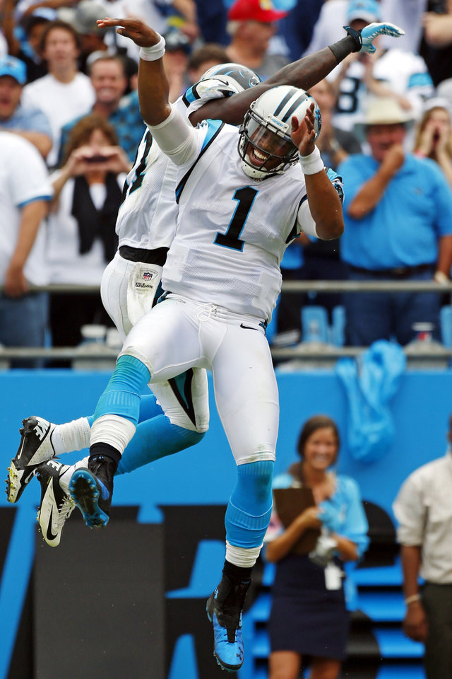Photo -   Carolina Panthers quarterback Cam Newton (1) celebrates his touchdown run with a teammate during the fourth quarter of an NFL football game against the New Orleans Saints in Charlotte, N.C., Sunday, Sept. 16, 2012. The Panthers won 35-27. (AP Photo/Bob Leverone)